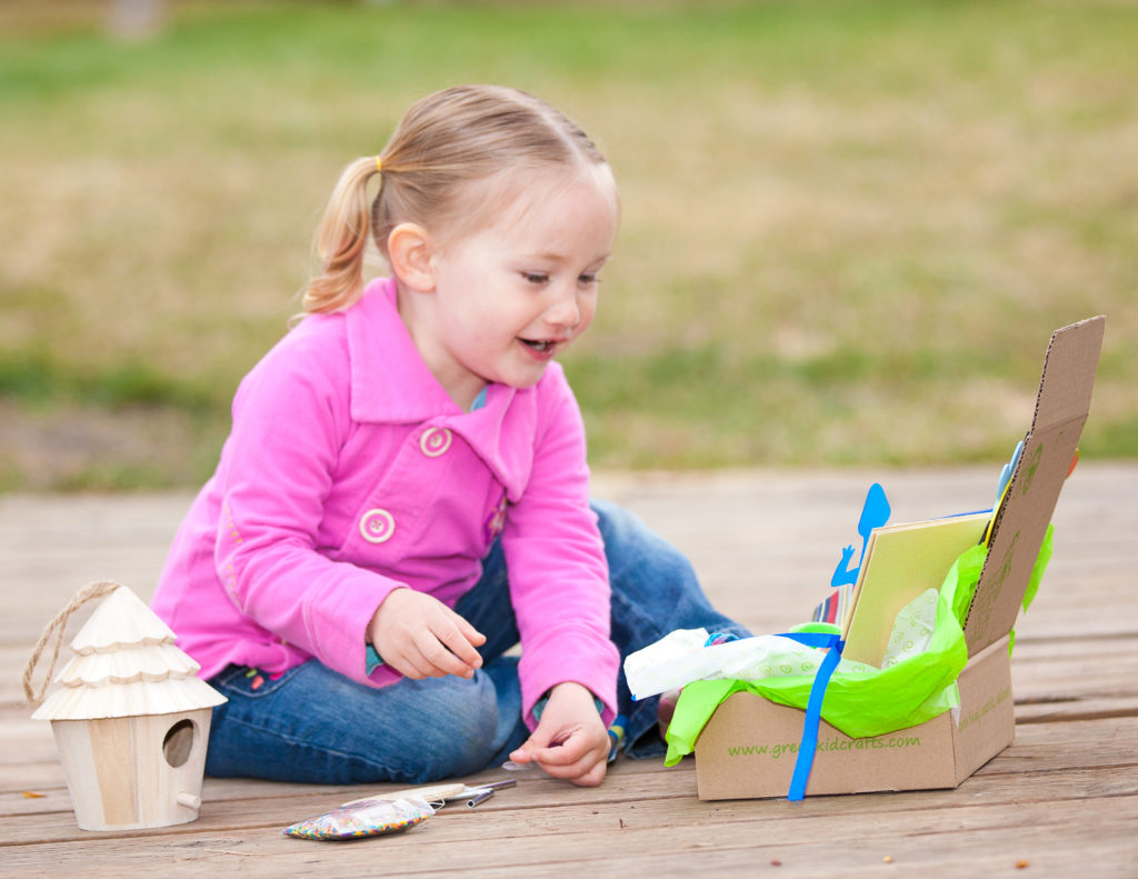 Girl with giftwrapped Green Kids Crafts discovery box