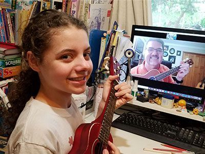 girl playing guitar with outschool teacher